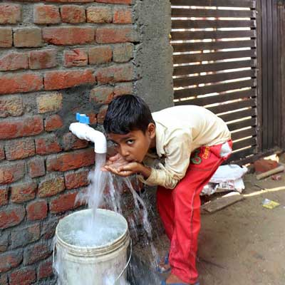 Fresh water bore well in India with boy drinking