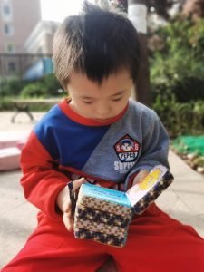 Boy playing with square toy